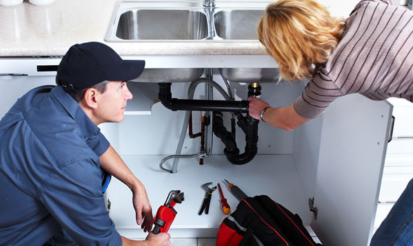 plumber discussiing sink problems with woman