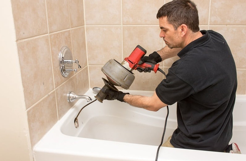 plumber using a plumbing snake to unclog drainage